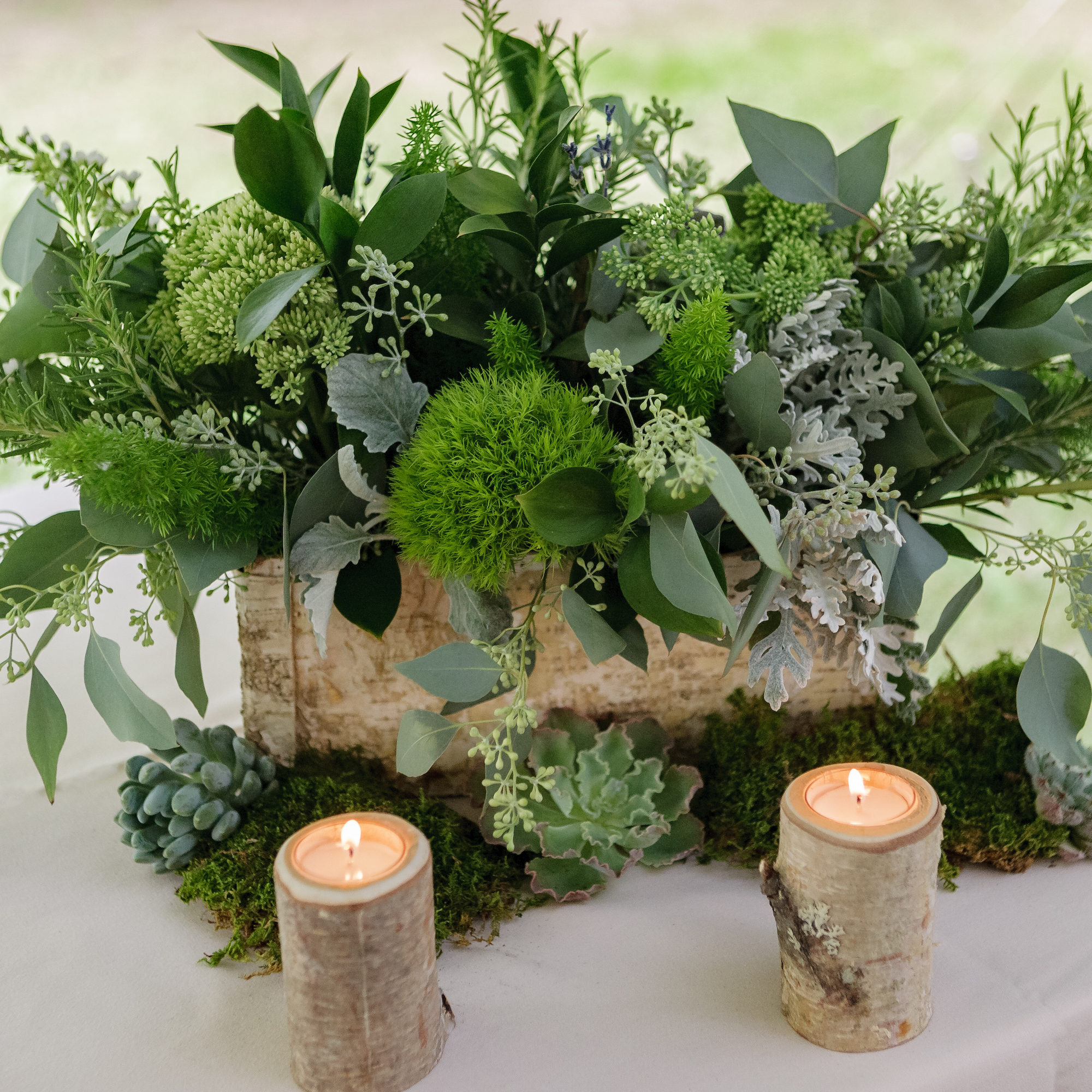 table centerpiece with dar green floral arrangment